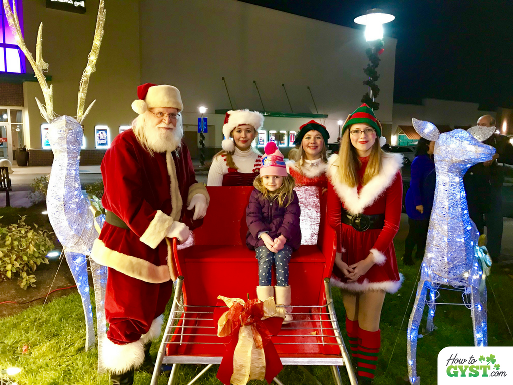 December 2017 wrap-up post for HowToGYST.com – Christmas Festival at Anderson Towne Centre, Scout sitting in Santa's sleigh, with Santa and elves